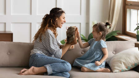 Mother and little daughter wear crowns sitting on sofa playing with hand puppet soft toys. Parent in game teaches develops preschool child telling tale about animals, have fun with kid at home concept
