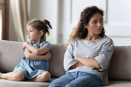 Mother disobedient daughter sit apart on sofa with arms crossed posture of discontent, think feels frustrated. Challenges of kids raising, lack of emotional bonding, child-rearing difficulties concept