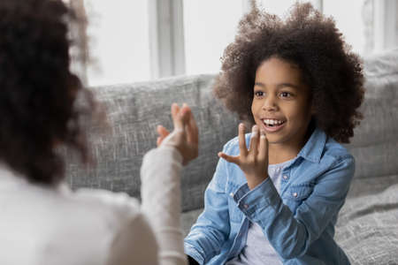 Happy adorable mixed race little girl learning correct sounds pronunciation with professional therapist at meeting. Smiling small biracial daughter practicing visual-manual communication with mother. Imagens
