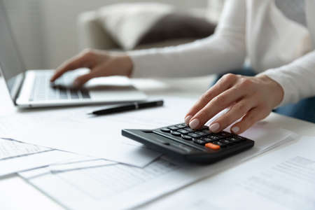 Close up young woman using calculator and computer software banking applications, managing monthly budget indoors, planning investment, loan payments, medical insurance or education expenditures. Banque d'images