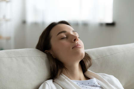 Close up head shot tired millennial woman leaning on cozy couch, enjoying lazy stress free weekend time at home. Tranquil peaceful young girl napping with closed eyes on sofa, daydreaming indoors.