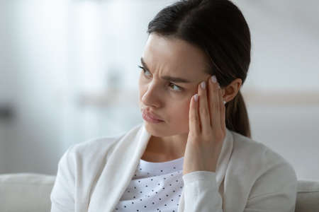 Head shot close up frustrated unhealthy woman touching temples, suffering from strong migraine or severe headache indoors. Stressed millennial girl thinking of hard difficult decision alone at home.