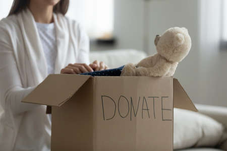 Close up on carton donation box with children stuff, preparing clothing and toys for orphans needy kids. Kind female volunteer put things for poor families in charity package, reuse recycle concept.