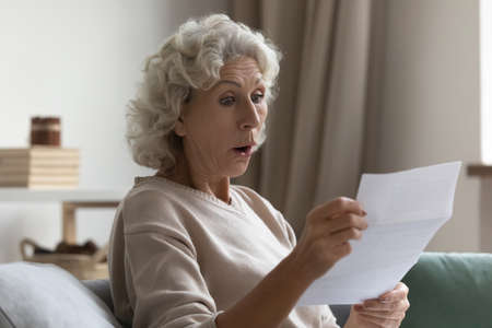 Amazed shocked mature woman with wide open eyes and mouth reading letter close up, holding paper notification in hands, sitting on couch at home, overjoyed middle aged female received unexpected news