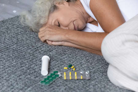 Close up depressed mature woman lying on bed with open bottle of pills, stressed frustrated middle aged female suffering from insomnia or depression, psychological problem, overdose concept