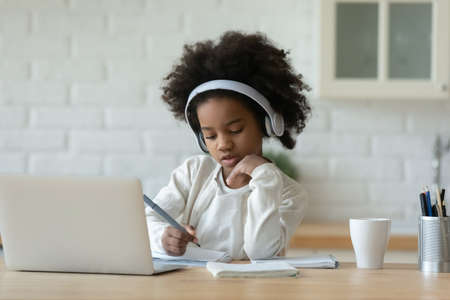 Focused little 7s mixed race child girl wearing wireless headphones, listening educational online lecture on computer, studying remotely writing notes in copybook, e-learning distant education concept Foto de archivo