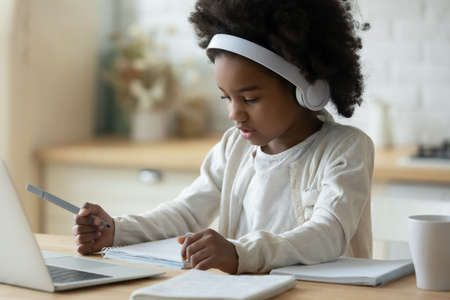 Concentrated little cute african american small child girl in modern wireless headphones sitting in front of computer, checking tasks at online school class, e-learning distant education concept.