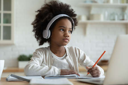 Distracted from learning little mixed race kid girl in headphones looking away, feeling tired. Thoughtful biracial small primary school learner stuck with difficult task homework, e-learning concept.