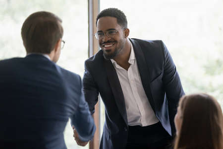 Happy diverse businessmen shake hands greeting get acquainted at business meeting in office. Smiling multiracial male partners or colleagues handshake close deal after successful negotiation.