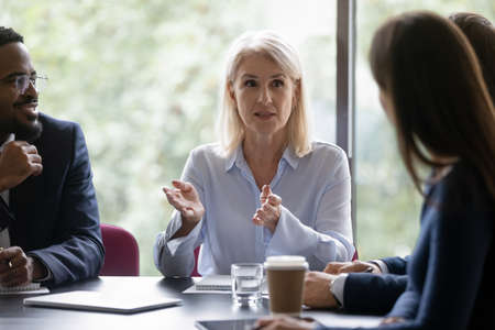 Motivated middle-aged Caucasian businesswoman lead hold team meeting with colleagues in office. Successful senior female boss or CEO talk with businesspeople at briefing, discuss ideas together. Stock fotó