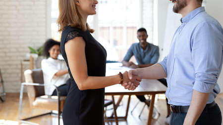 Smiling Caucasian businessman shake hand get acquainted greeting successful female employee at meeting, happy diverse colleagues handshake close deal make agreement in office, partnership concept