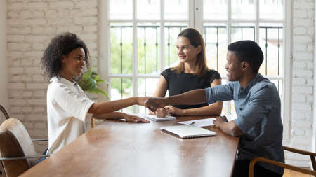 Smiling employer shake hand greet get acquainted with confident African American female job applicant, excited recruiter handshake biracial woman candidate congratulate with successful work interview