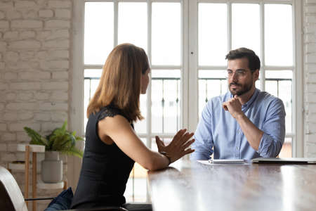Caucasian female job candidate talk with middle-aged businessman make good first impression at interview in office, diverse focused business partners speak negotiate at meeting or briefing Stock Photo