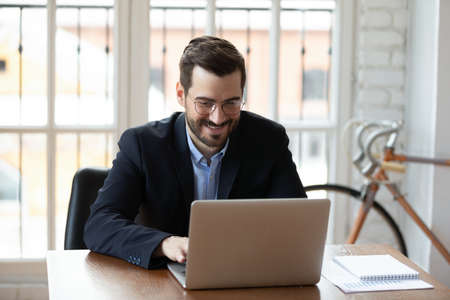 Smiling middle-aged Caucasian businessman in glasses sit at desk work on laptop in office, happy young male boss or CEO busy browsing Internet on modern computer, new technology concept