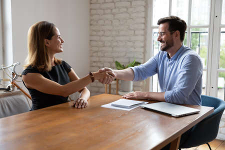 Smiling diverse business partners shake hands greet get acquainted at office meeting, happy male recruiter or employer handshake confident woman candidate or applicant congratulate with employment