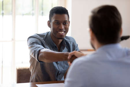 Smiling African American male employee handshake coworker get acquainted greeting at meeting, happy biracial man worker shake hand congratulate male colleague with promotion at briefing
