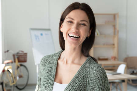 Head shot portrait overjoyed smiling young businesswoman standing in modern office, beautiful happy female employee intern looking at camera, business coach mentor posing for corporate photo