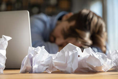 Close up crop view of draft paper on forefront on office desk. Tired male employee fall asleep doze off overwhelmed at workplace. Exhausted man worker sleep at table. Overwork, fatigue concept.