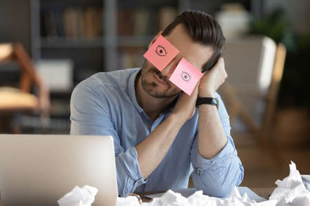 Tired Caucasian male worker fall asleep at workplace in office, have sticker pads on eyes. Exhausted young man take nap doze off sleep at desk, overwhelmed with work. Fatigue, exhaustion concept. Imagens