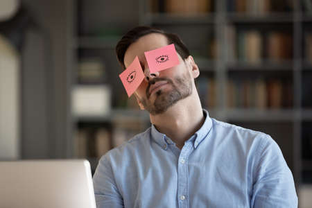 Exhausted young Caucasian man worker have sticker pads on eyes sleeping near computer in office. Tired millennial male employee fall asleep doze off at workplace, feel overwhelmed drained at work.