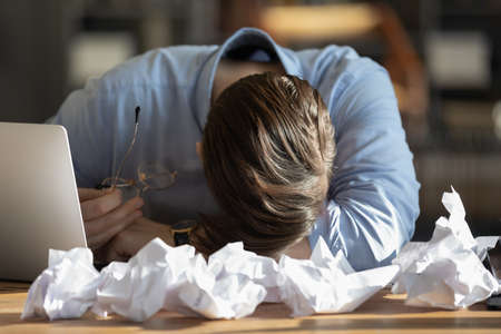 Exhausted male employee fall asleep doze off at desk at workplace overwhelmed with work amount. Tired man worker sleep at table at office, overwork before deadline. Fatigue, time management concept.
