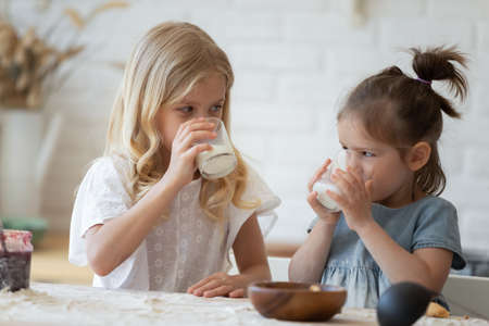 Two little sisters drinking eco milk from glasses at a messy, flour-covered table in kitchen. Happy 5 and 8-year-old siblings having a break and enjoying wholesome cow milk after making tasty cookies