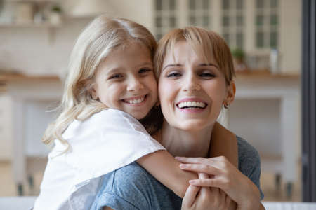 Happy preschool daughter embracing her good looking young mommy, both looking at camera and smiling. Cheerful mom and child enjoying free time together