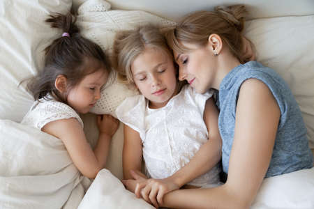 Young mother and little children sleeping quietly on soft white pillows. Mom in her 30s and her 5 and 8 year old daughters in casual clothes napping together under soft white comforter. Top view