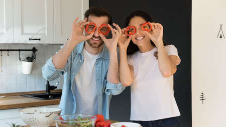 Portrait of overjoyed Caucasian young couple tenants have fun make funny faces cooking together at home. Smiling man and woman enjoy preparing healthy tasty food in kitchen on lazy family weekend.