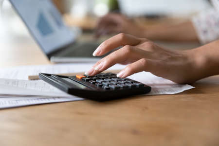 Crop close up of woman calculate on calculator manage household finances expenditures at home. Female pay bills taxes online, take care of family budget, consider financial expenses. Saving concept.