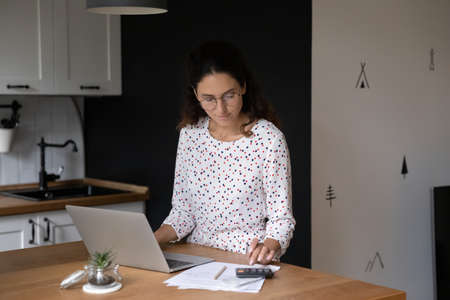 Focused young Caucasian woman in kitchen manage household family budget calculating expenses on calculator. Millennial wife pay bills taxes online on laptop, take care of expenditures at home.