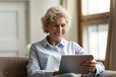 Modern day pensioner. Happy laughing old woman spending free time at home with touch screen tablet computer making video call to relatives, reading email with good news, visiting hobby internet sites