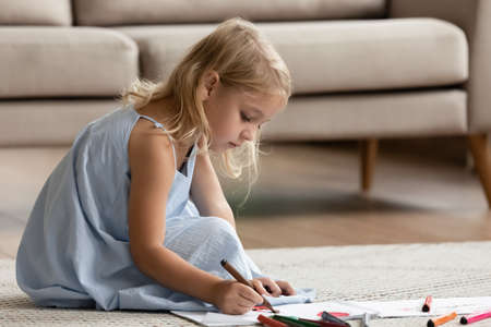 Talented artist. Inspired attentive little preschool child girl sitting on warm floor in cozy apartment painting funny pictures with fiber-tip pens, drawing bright imaginary world on piece of paper