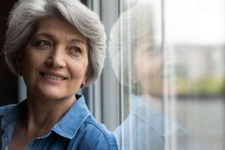 Close up of dreamy elderly Caucasian grey-haired woman look in window distance thinking or visualizing. Happy mature 60s female lost in thoughts, dreaming or imagining bright healthy future.