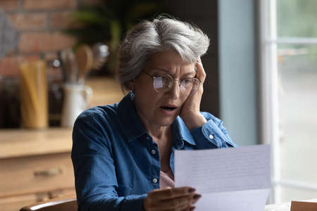 Unhappy mature Caucasian 60s woman in glasses read post paper letter shocked by bad news. Distressed senior grey-haired female surprised stressed by negative message in postal correspondence.