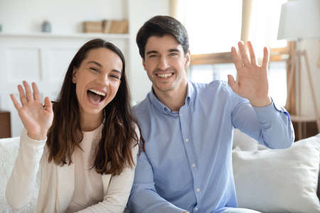Greetings to all! Smiling millennial blogger family sitting on couch at living room recording vlog waving hand to subscribers looking at camera, calling by video link, taking part in virtual event