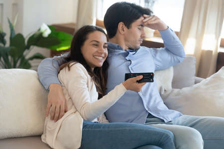 Young couple with divergent interests watch tv together, happy smiling wife chooses soap opera, romantic movie or reality show with pleasure while bored dull indifferent husband having nap turns away