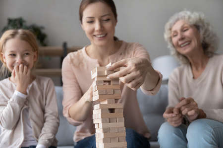 Close up three generations of women playing stack and crash board game together, smiling young woman with little daughter and mature mother building wooden tower, having fun on weekend at home