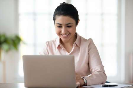 Smiling indian millennial female employee sit at desk in office look at laptop screen consult client online. Happy young ethnic businesswoman or worker busy typing working on computer at workplace.