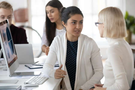 Focused multiethnic colleagues sit at desk in coworking office discuss business project or idea together. Diverse female coworkers talk brainstorm cooperating at PC at workplace. Teamwork concept.