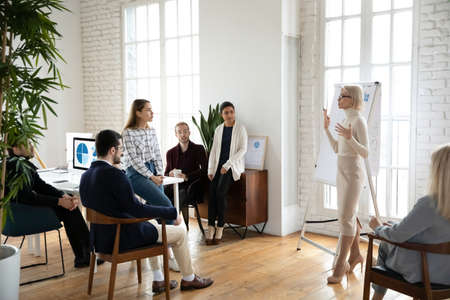 Confident young Caucasian female coach or speaker talk make flip chart presentation at office meeting. Millennial businesswoman lead briefing with colleagues, present project on whiteboard. Foto de archivo