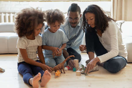 Full length happy african american married couple playing toys with cheerful small children siblings, sitting together on warm wooden floor in living room, affectionate loving family weekend pastime.