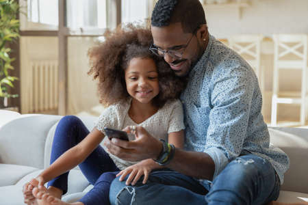 Happy young african ethnicity dad relaxing on sofa with adorable small kid daughter, using smartphone applications together indoors, smiling family recording funny video or making selfie photo.