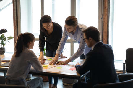 Focused young multiracial manager developing marketing strategy with skilled male leader, writing goals or ideas or colorful sticky paper, attached to reports and documents, brainstorming activity. Stock fotó