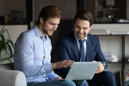 Two smiling businessmen in formal wear sitting on comfortable sofa with laptop, discussing good project results or brainstorming ideas in modern office, collaboration corporate partnership concept. Reklamní fotografie