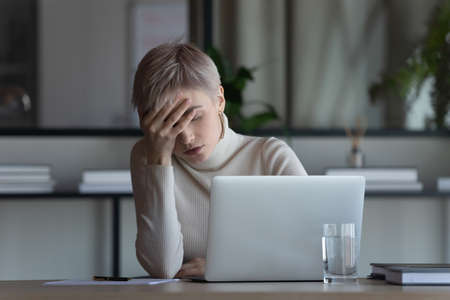 Tired young Caucasian female employee fall asleep doze off sitting at desk working on computer in office. Exhausted 30s businesswoman sleep at workplace, suffer from overwork. Fatigue concept. Imagens