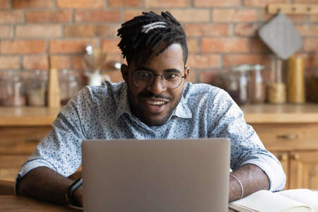 Stunned young African American man in glasses look at laptop screen shocked by unexpected sale deal or offer online. Stunned biracial male surprised by unbelievable news or email on computer. Stockfoto