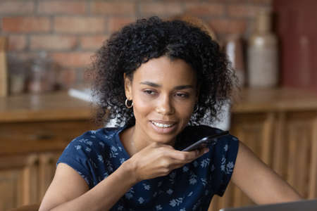 Young African American woman talk speak record audio message on modern smartphone gadget at home office. Millennial biracial female employee activate digital voice assistant application on cellphone.