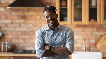 Portrait of smiling millennial African American man in glasses pose in modern renovated home kitchen. Happy young 20s biracial male tenant or renter in spectacles satisfied with good quality service. Stockfoto
