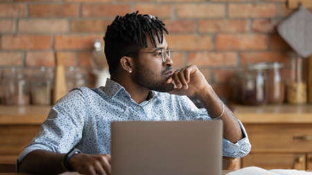 Pensive young biracial man distracted from computer work look in distance think ponder. Thoughtful African American 20s male lost in thoughts, planning or visualizing at home office. Vision concept. 免版税图像